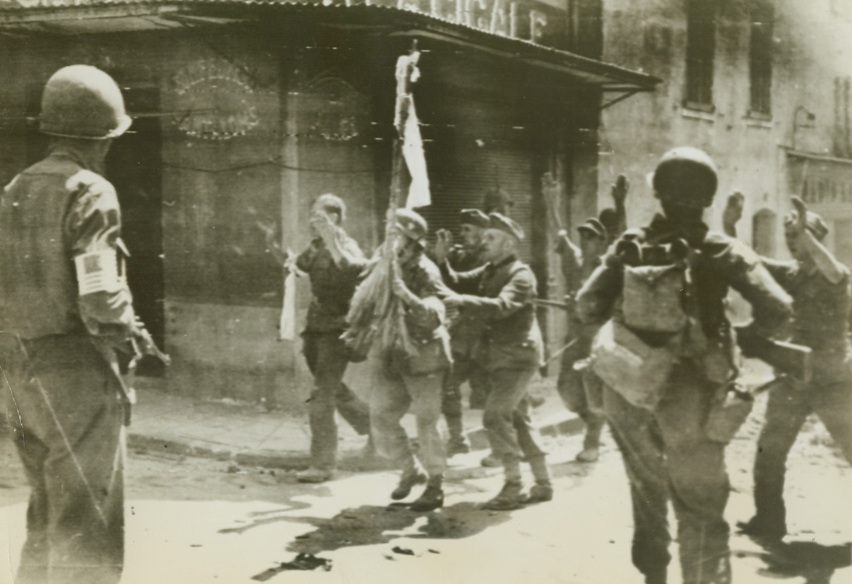 """New Nazi's """"Standard"""", 8/17/1944. France – While one of their number holds the white flag of surrender aloft, Germans rush out to give themselves up to American troops at a street corner in a little town east of Toulon. Note how two of the Nazis hide themselves behind the flag bearer – as though they expected to feel lead from Yank guns at any moment. (Passed by Censors) Credit: ACME photo by Sherman Montrose for War Picture Pool;"""