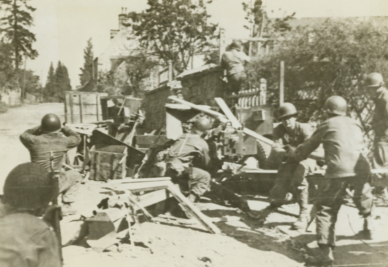 Awaiting Counter-Attack, 8/12/1944. France – Their anti-tank gun camouflaged with crates and boxes, this Allied gun crew stands ready on the outskirts of recently occupied Cherence Le Roussel, silently awaiting Nazi counter-attack. Credit: Signal Corps Radiotelephoto from ACME;