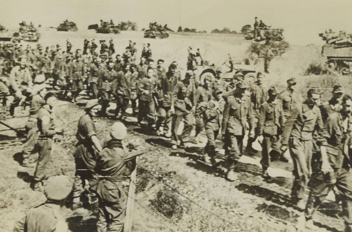 Two-Way Traffic, 8/23/1944. France – Past a long column of dejected German prisoners being marched to the rear, British armored vehicles rumble ahead toward the front. Nazis were taken when the Falaise-Argentan Gap was closed by Allied Forces cutting off any possible escape route for an estimated 100,000 Germans. Credit: British War Office photo via Army Radiotelephoto from ACME;