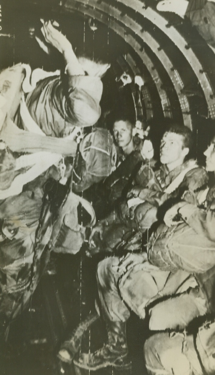 To Leap Into France, 8/15/1944. Hard and rugged Paratroopers listen intently to the Jumpmaster (standing) as he gives last minute instructions while their C-47, part of the Troop Carrier Air Division of the 12th Air Force, heads toward the dropping zone in southern France. Credit: Army Radiotelephoto from ACME;