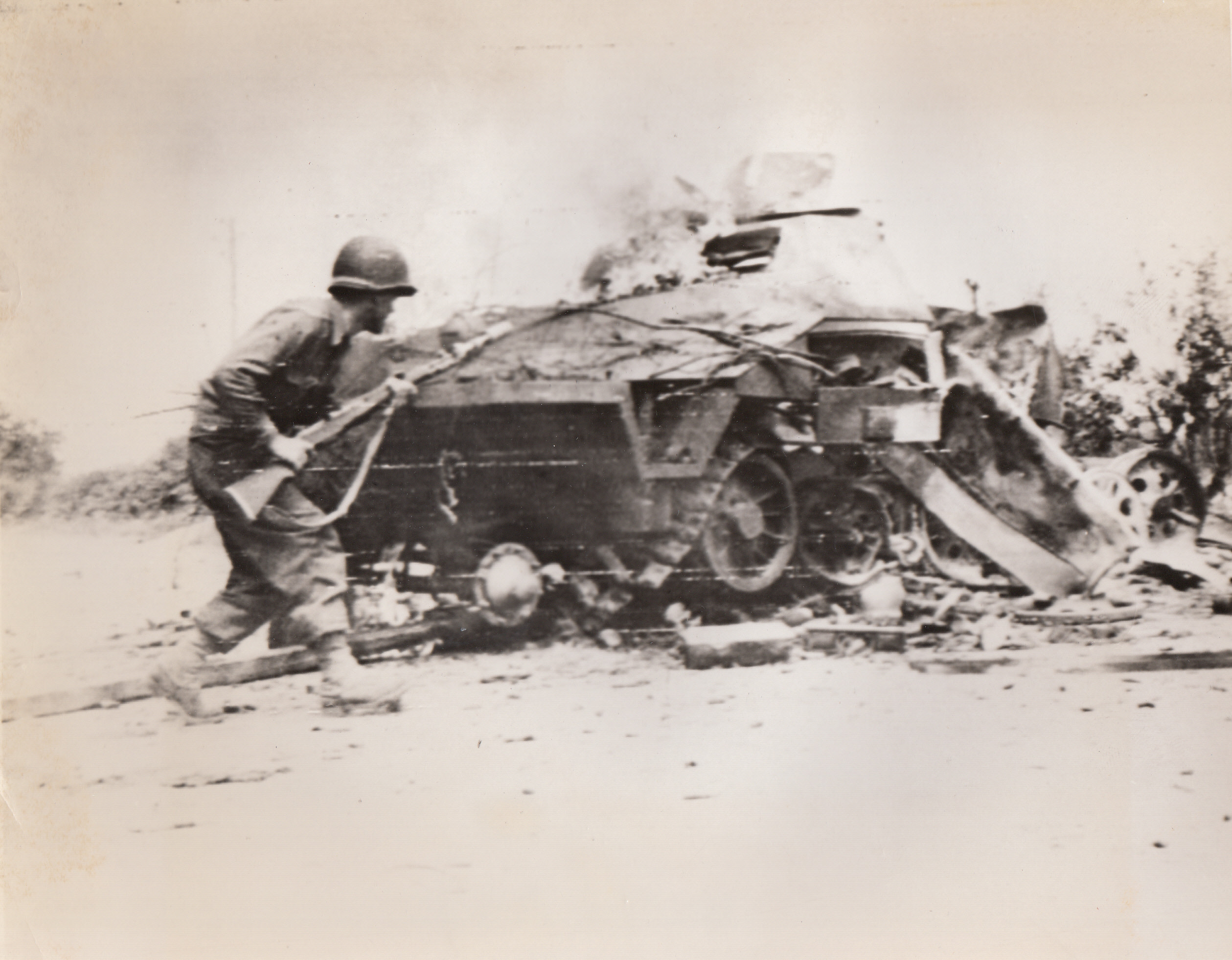 Lesson In Caution, 8/14/1944. France – With cautious step, Sgt. Andrew Harding, Bridgeport Conn., approaches a burning Nazi armored car. The vehicle had been knocked out on the road to La Mont by an American three-inch shell.;
