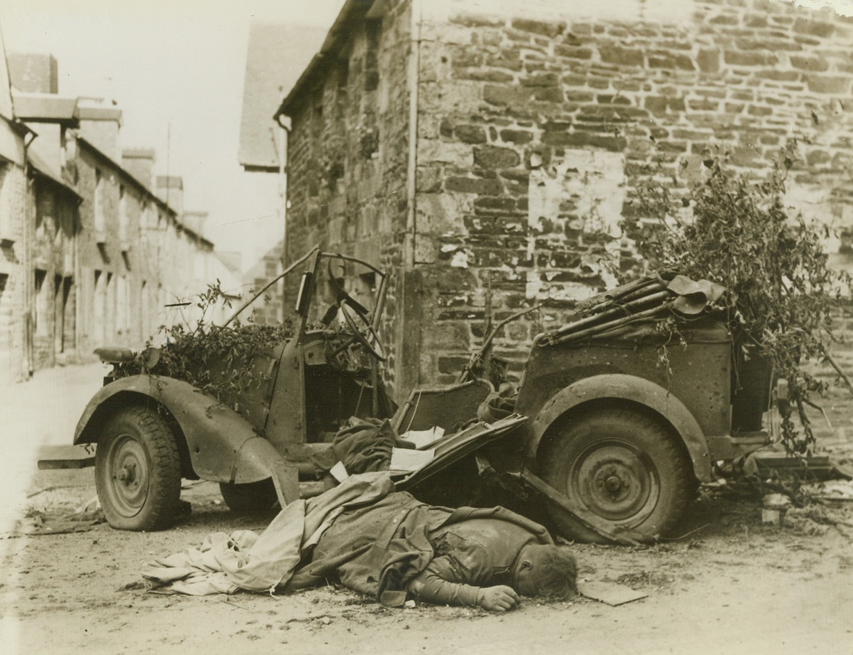 Nazi Reaches End of Journey, 8/15/1944. France – Face down in the dust of a road, a German soldier lies dead beside his Volkswagon in Barenton, France. Marks of blood line his face. American troops took the town in latest drive through France. Credit: Signal Corps photo from ACME;