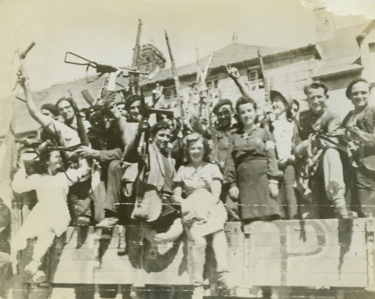 Hunting Party Searches Nazis, 8/18/1944. France – Waving captured German guns enthusiastically, these fighting Frenchmen and women of the town of Rostrenen ride off to round up stray Nazis in the vicinity after the Yanks had wiped out most of the resistance. Credit: Army photo from ACME;