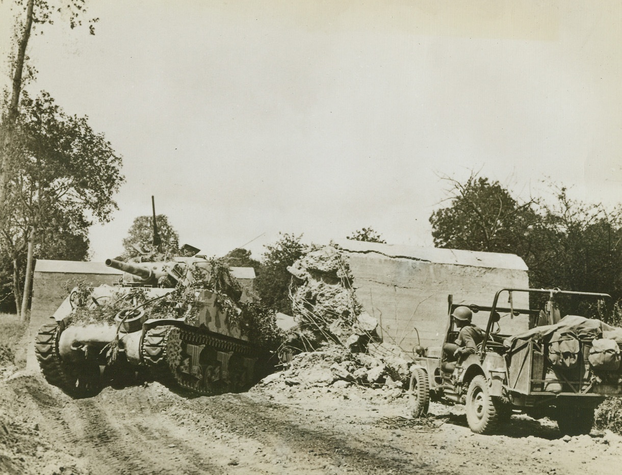 Road Block No Obstacle, 8/5/1944. France – An American tank smashes through a road block on its way to join the American lightning attack on the Avranches sector during the current offensive in Brittany. Tank is camouflaged with twigs and paint. Note how the so-called block is completely demolished. Credit: ACME;