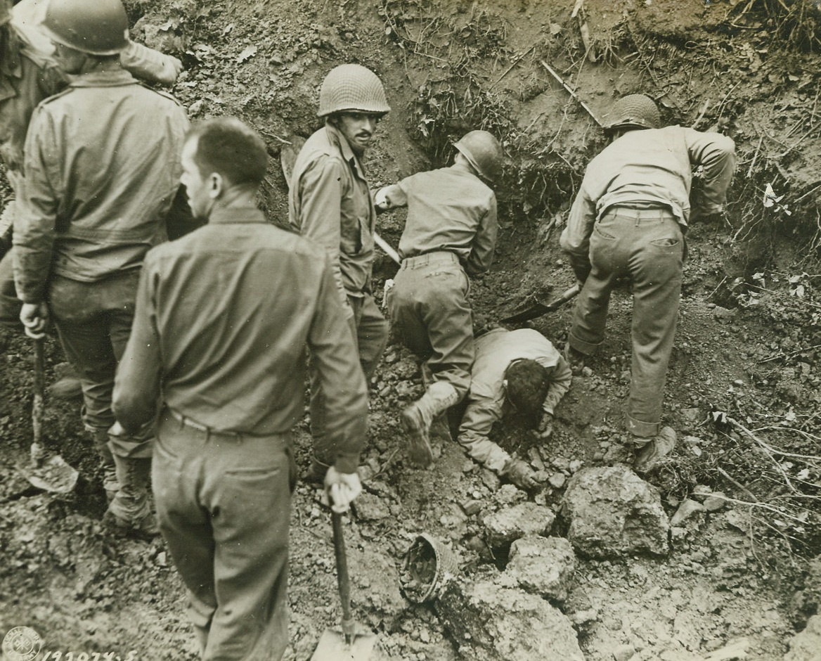 Medics to the Rescue, 8/7/1944. Somewhere in France – Working feverishly with their shovels, medical men attached to an infantry unit serving in France dig out some of their men who were buried beneath an avalanche of dirt when enemy shells struck. Credit: US Army photo from ACME;
