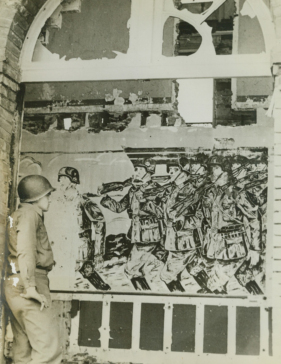 Nazi Victory Painting Premature, 8/4/1944. France – In a captured German headquarters in France an American soldier examines with interest an unfinished painting of German troops marching in victory. Nazis did not have time to complete it before evacuating before the relentless drive of the Allies. Shell fire has knocked holes in the mural. Credit: ACME;
