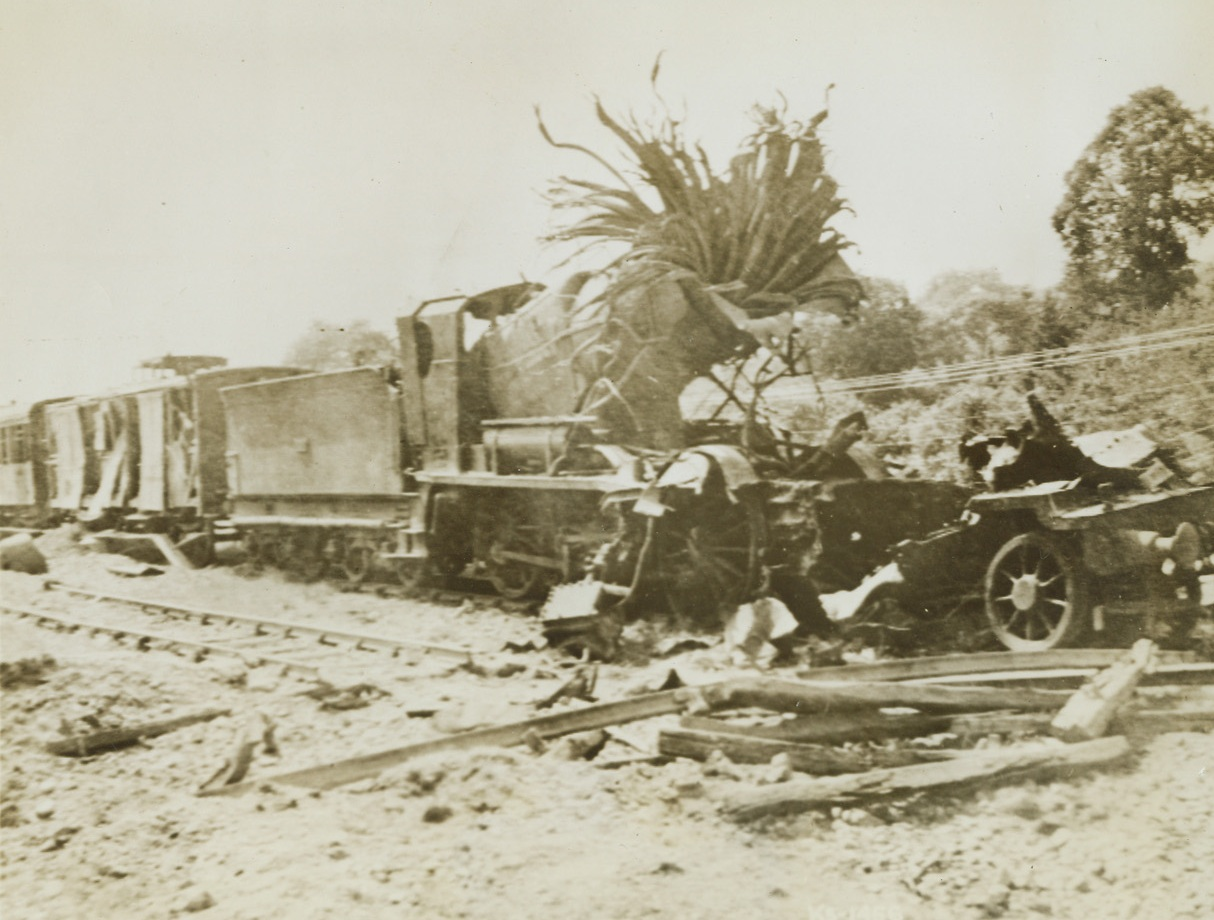 Shattered Nazi Rail Linem, 8/5/1944.France – Twisted steel is all that remains of this Nazi locomotive after an American dive bomber let loose its load of destruction. Continual hammering at Nazi rails has considerably hampered their movement of supplies and troops. Credit: Army photo from ACME;