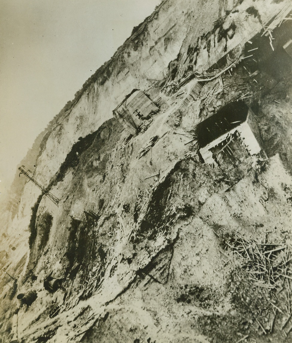 """RAF Scores Double Hit On Underground Target, 8/1/1944. Pas De Calais, France – Hidden in a quarry in the Pas De Calais area, German underground installations reputed to be connected with their long-range rocket planes, were attacked by the RAF """"heavies"""" in successive raids on July 17 and July 20. In between the two raids, TODT organization workers sought to repair the damage from the first, but this photo, taken after both attacks, shows timber props used in reconstruction work scattered in all directions. The concrete dome situated on the cliff has a huge gap in the ground supporting it, and other concrete structures have been torn away by the 12,000-pound bombs. For photo of the dome before the raid, see ACME photo # BP 732303. Credit: British Official photo from ACME;"""
