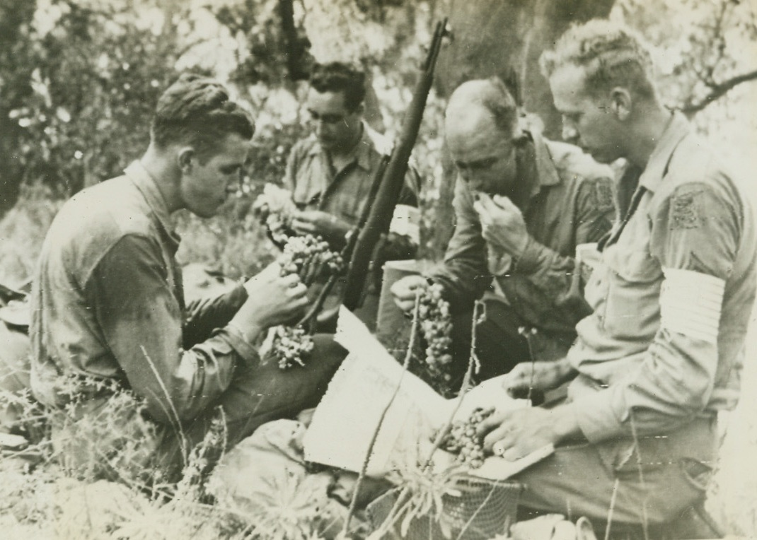 Grapes In Southern France Not Sour, 8/18/1944. France – Four American soldiers relax after storming the beaches of Southern France and dig into some of the famed French grapes found along the Riviera. Eating with relish are (left to right): Pvt. Donal Cheperka, Elgin, Ill.; Sgt. Antonio Oppio, Reno, Nev.; Cpl. William T. Pribble, Nocona, Tex.; and Cpl. John Uecker, Marshall, Minn. Cpl. Uecker studies a map while enjoying the fruit. Credit: Army Radiotelephoto from ACME;