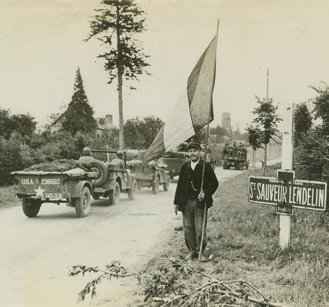 Tricolor Salute, 8/8/1944. France – An American Armored Division receives a greeting from this old French man with a Tricolor on a staff, as it rolls into St. Sauveur Lendelin. Credit: ACME;