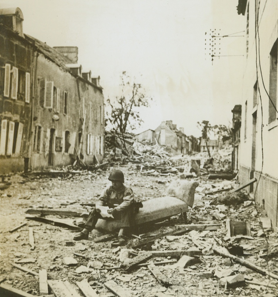 A Bit of Home in France, 8/9/1944. France – Amid the destruction and ruin of St. Sauveur Lendelin, Cpl. Floyd Davis, Nashville, Tenn., sits on an old settee and reads a letter from home. A bit of home injected into this scene of warfare makes for contrast and relief from thoughts of death, destruction, and disaster. Credit: ACME;