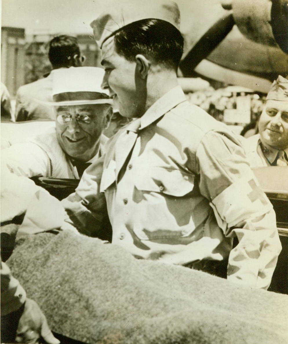 President Chats With Saipan Casualty, 8/10/1944. Hawii-- President Roosevelt (Left Background) chats with a wounded soldier (On Stretcher) at an airfield in Hawaii, during the Chief Executive's recent visit there. The wounded man, whose face has been deleted by censors, has just been flown in from Saipan. 8/10/44 (ACME);