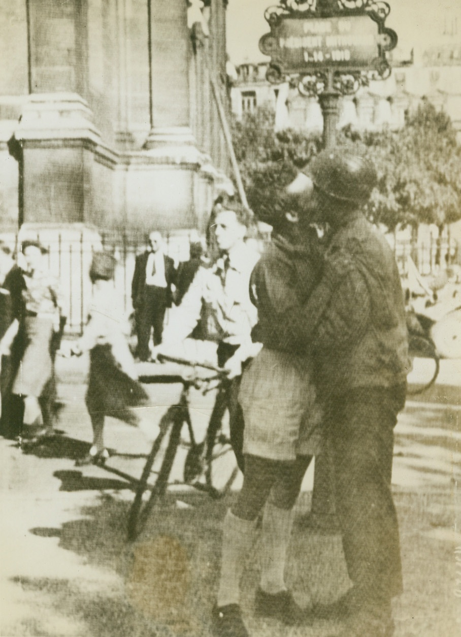 Not Amour – Gratitude, 8/28/1944. Paris – In gratitude for the liberation of his beloved capital, a French civilian gives the traditional exuberant greeting to a Maquis, a member of the French forces which drove the Germans from Paris. Civilians, accustomed to such scenes, pass by with hardly a glance. Credit: Signal Corps Radiotelephoto from ACME;