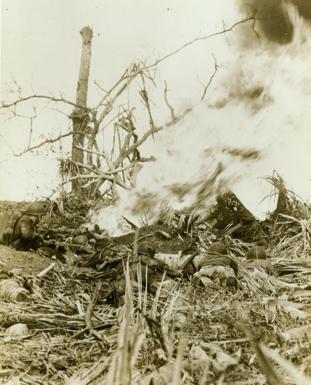 Burn Japs Out of Hiding, 8/2/1944. Guam-- While a Marine (Left) uses a flame thrower to burn the enemy out of a hidden pillbox on Guam, his buddies wait with guns poised for the Japs to show themselves. Although surrounded by leathernecks, the Japs refused to Surrender. (ACME);