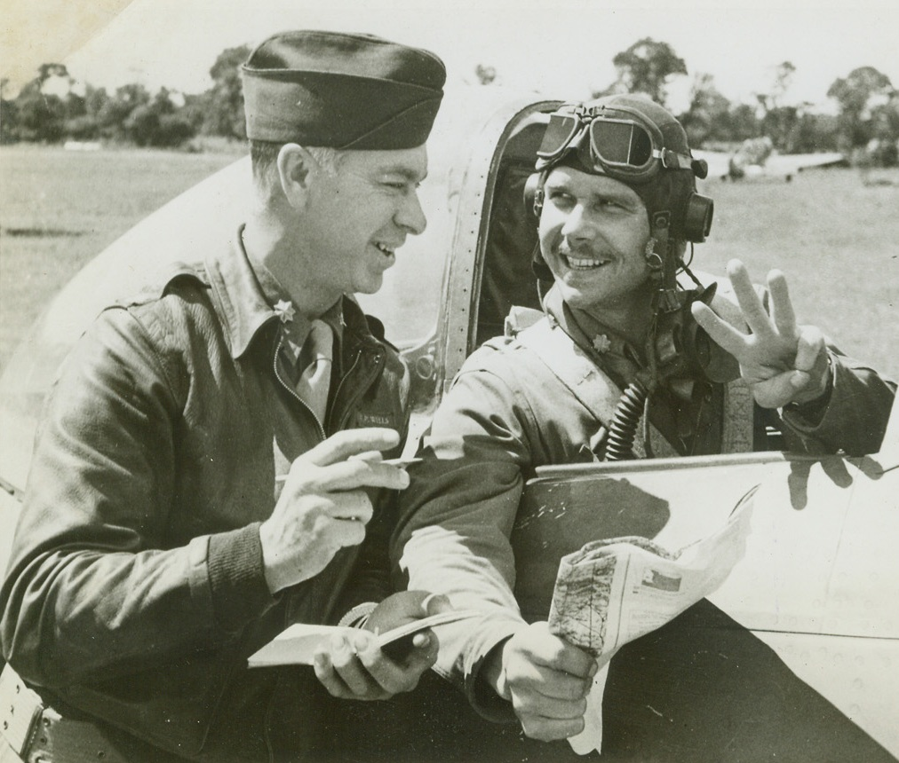 Three Planes, Sir, 8/8/1944. France – Returning from a mission in Normandy, Maj. Rockford V. Gray, Dallas, Texas, reports to Intelligence Officer Maj. Perry Wells, Chicago, Illinois, his quota of three German planes downed during the flight over British lines. These three brought Maj. Gray's score of planes downed to seven. He has flown 102 combat missions and 182 sorties. Credit: ACME;