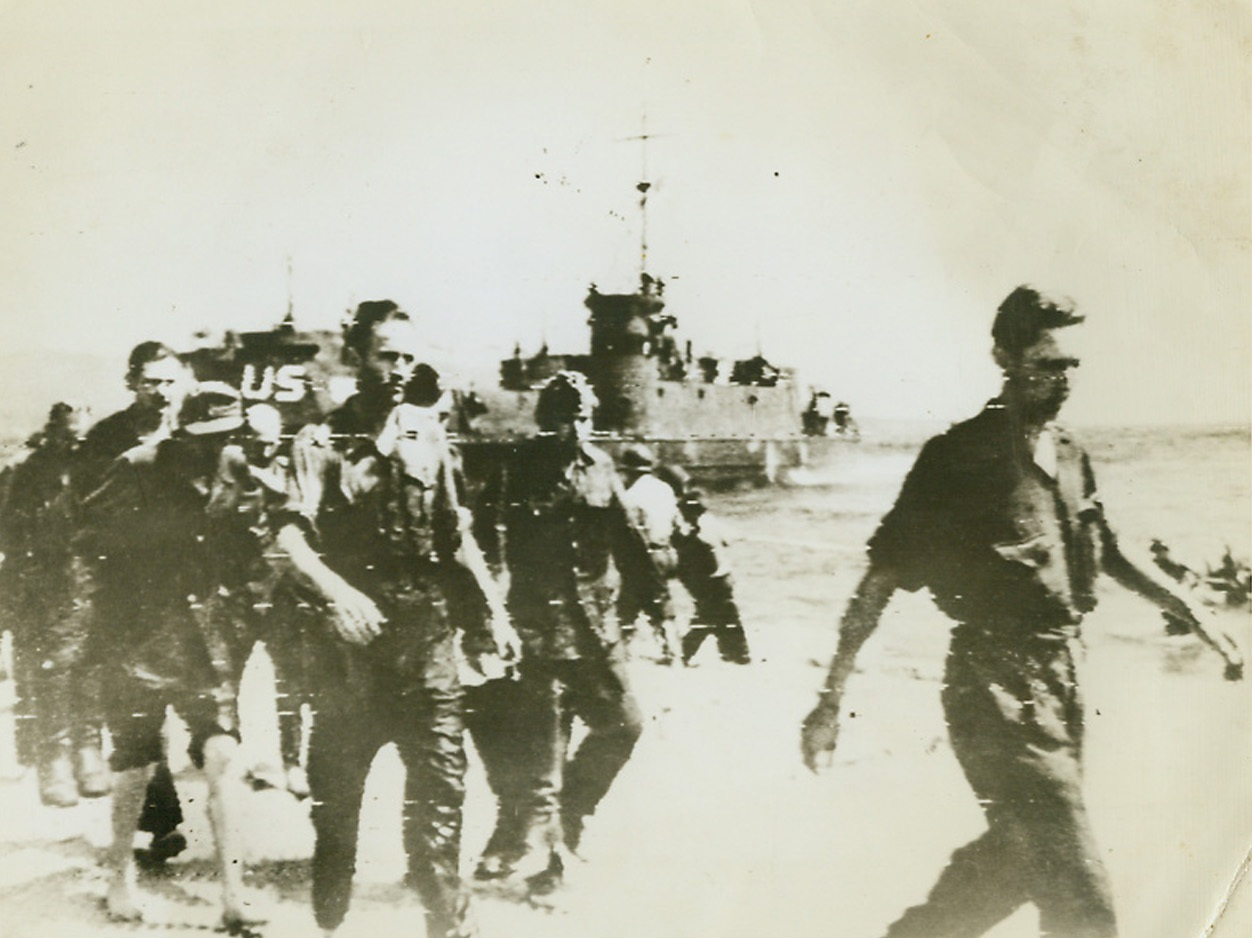 First Prisoners in New Invasion, 8/16/1944. France – As Allied troops come ashore from the LCIs in background, a group of Germans—first prisoners taken in the invasion of Southern France—march along the beach under guard. Credit: Army Radiotelephoto from ACME;