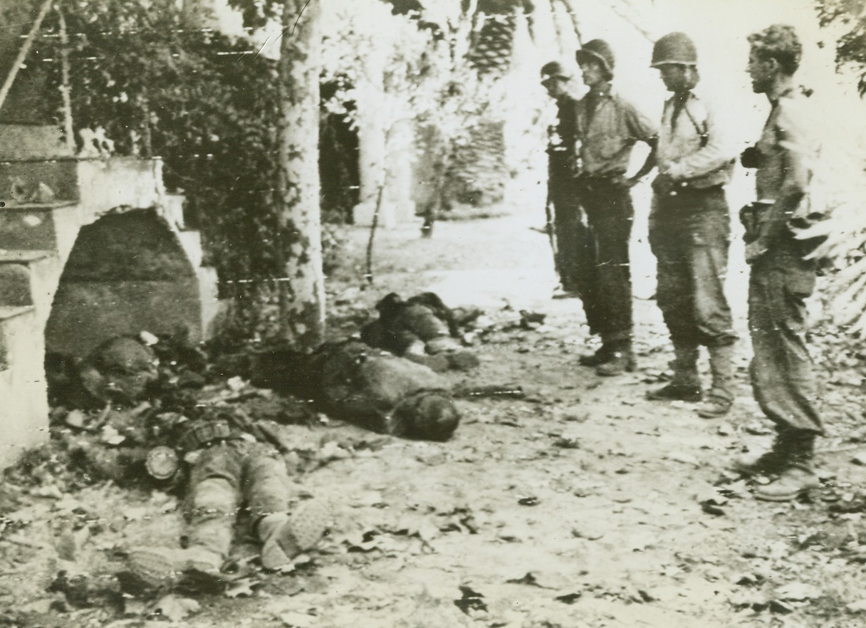 Nazis Killed in New Invasion, 8/16/1944. France – U.S. soldiers (right) solemnly view the bodies of German soldiers killed in this Allied landing east of Toulon, in Southern France. Having secured their beachhead, Allies are driving inland proceeding according to plan. Credit: Army Radiotelephoto from ACME;