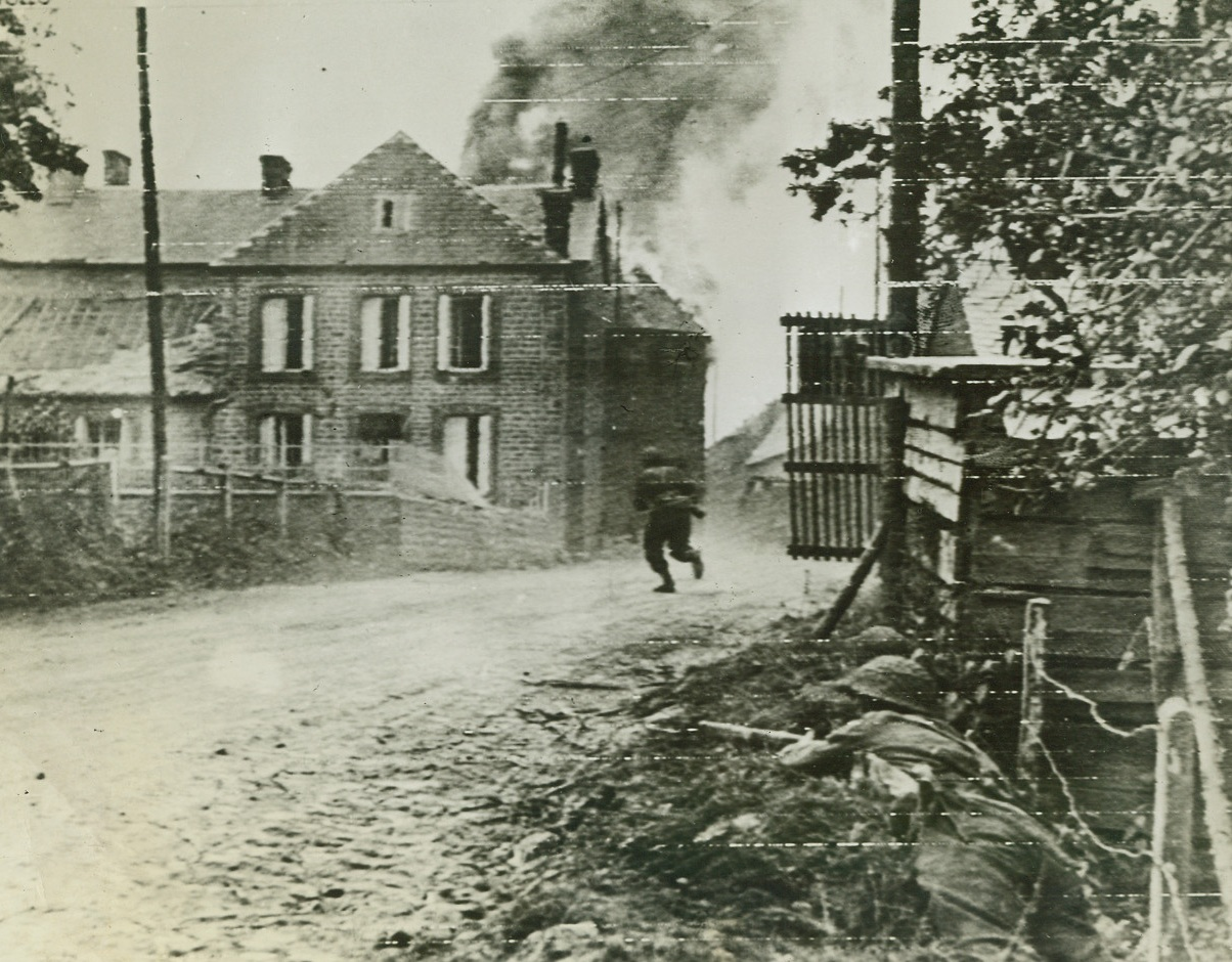 Looking for Snipers, 8/8/1944. France – A British infantryman, his gun held ready, dashes across a road in Montchauvet, while two of his buddies (right, foreground) cover him. The men are after snipers hiding in buildings in background. Credit: British War Office photo via Army Radiotelephoto from ACME;
