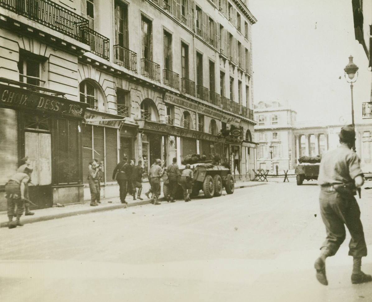 France Regains Its Chamber of Deputies, 8/30/1944. France – American and French troops deploy cautiously, taking what cover they can find behind armored vehicles, to attack a German garrison of some 400 men barricaded in the famous Chamber of Deputies in Paris. The Chamber is at the foot of this street. Credit: ACME;