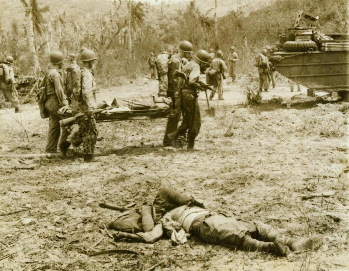 One of Many, 8/4/1944. Guam—US Marines move forward near Asan Point, carrying a litter of supplies to their forward troops. In the foreground is a dead Jap, one of the 7,419 enemy dead who have been buried by the Marines since they landed on the island. Although enemy resistance has stiffened, the American forces continue to advance unchecked. 8/4/44 (ACME);