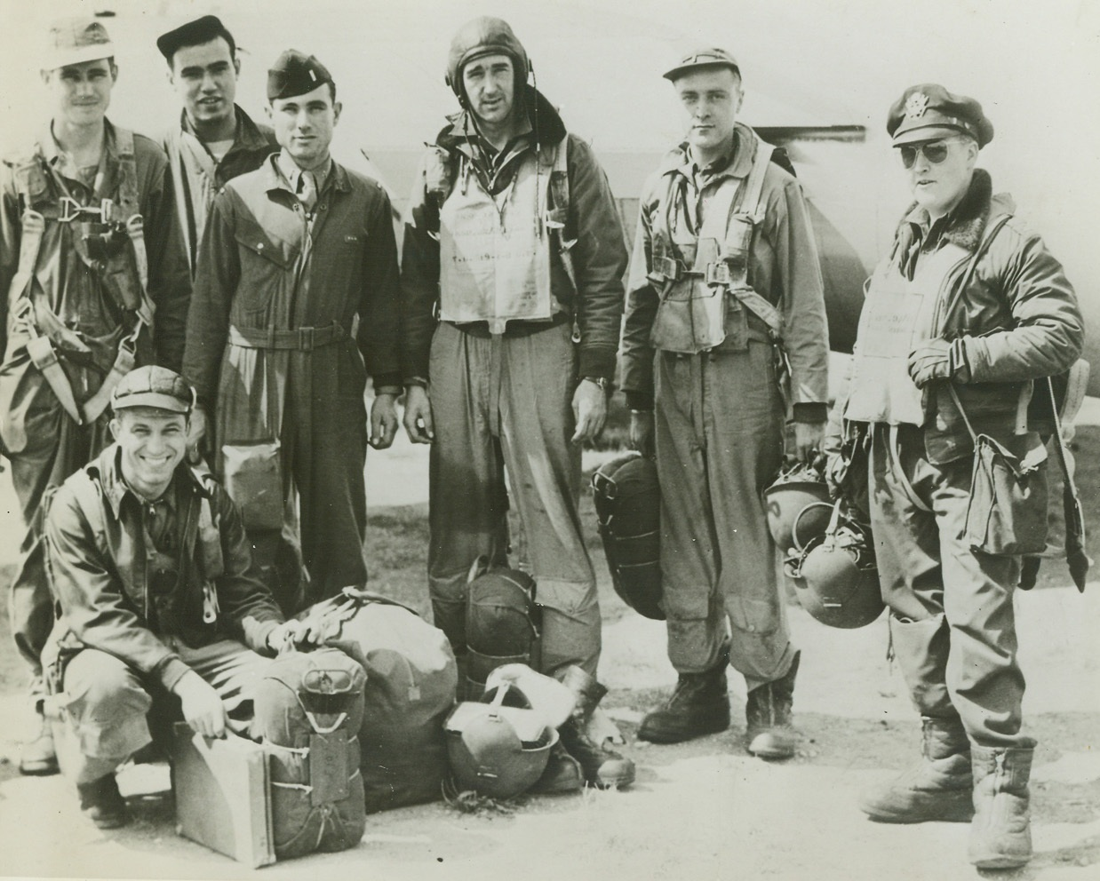 Back from Raid on Alsace Lorraine, 8/22/1944. England – American airmen return to their base in England after raiding targets in Alsace Lorraine. They are (left to right): S/Sgt. Henry L. Wolf, Coahoma, Texas; Sgt. Burdette E. Bonner, Galesburg, Illinois; S/Sgt. Robert B. Linnemann (stooping), Cincinnati, Ohio; 2nd Lt. Burnett L. Deyerle, Roanoke, Virginia; Joseph R. Lyons, Wooster, Massachusetts; 2nd Lt. Lorne R. Marlatt, Brooklyn, New York; and 1st Lt. Neil A. Daniels, Oak Park, Illinois. Credit: ACME;