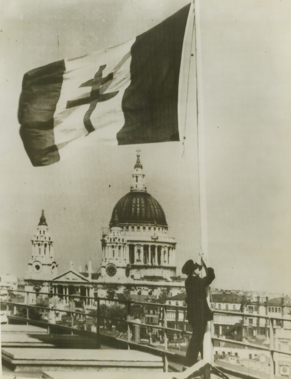 Marking Liberation of Paris, 8/23/1944. London – By way of celebration of the Liberation of Paris, Londoners hoisted a flag bearing the Cross of Lorraine to wave over the British capital. In the background is St. Paul's Cathedral. Credit: ACME Radiophoto;