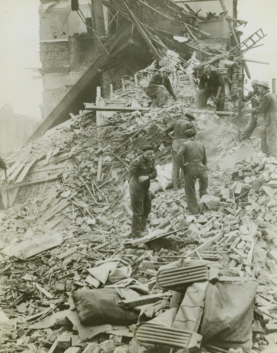 Robot Bombs Devastate Southern England, 8/7/1944. Southern England – While falling concrete and plaster raise a smoky haze, workmen search through the wreckage of homes for victims of the raid. A direct hit from one of the bombs has completely razed this house and only a wall of the one in the background remains standing. Credit: ACME;