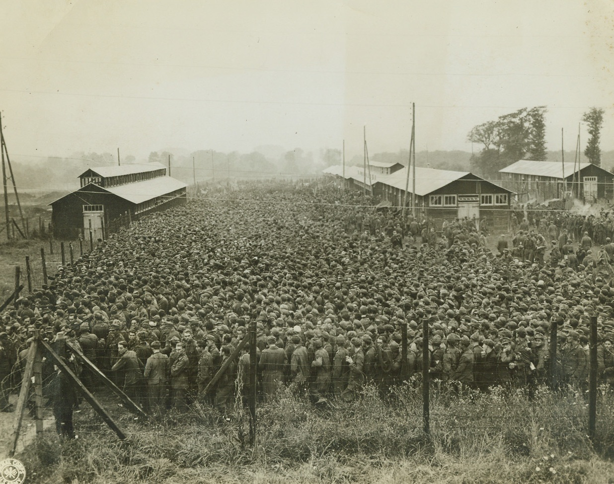 """Ten Thousand Hungry """"Supermen"""", 8/29/1944. France – In this compact mass, stretching far into the background, are ten thousand German prisoners, captured during the Allied drive in France. It's """"chow time"""" here, and they're lining up for their lunch in their stockade somewhere in France. Credit: Signal Corps Photo from ACME;"""