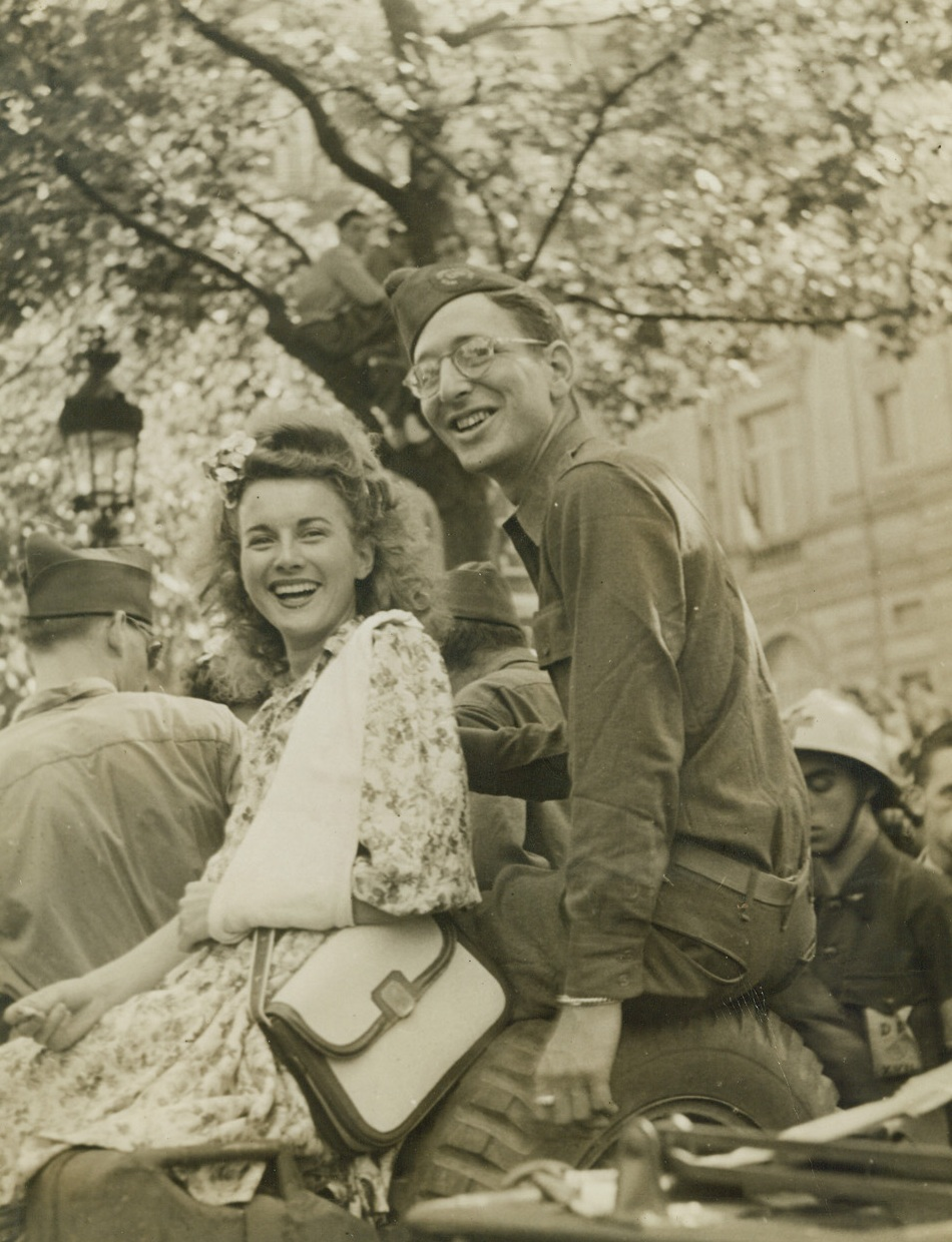 NEA Correspondent Does Himself Proud, 8/30/1944. France – Tom Wolf, NEA war correspondent, sits with his arm around a very beautiful French lassie whose heart he probably captured by offering her a lift in his jeep as liberating forces entered Paris. The blonde-haired beauty has her arm in a sling. Credit: ACME Photo by Bert Brandt, War Pool Correspondent;