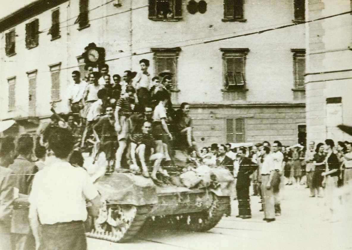 Joyous Welcome For British 8th Army, 8/14/1944. Florence, Italy—Joyous civilians jump on top this South African-manned tank as it enters Florence, while others cram the streets to watch the coming of the victors. After the British 8th Army had overcome all Nazi Resistance, AMU officials rushed in to give aid to the needy citizens. 8/14/44  Acme RadioPhoto;