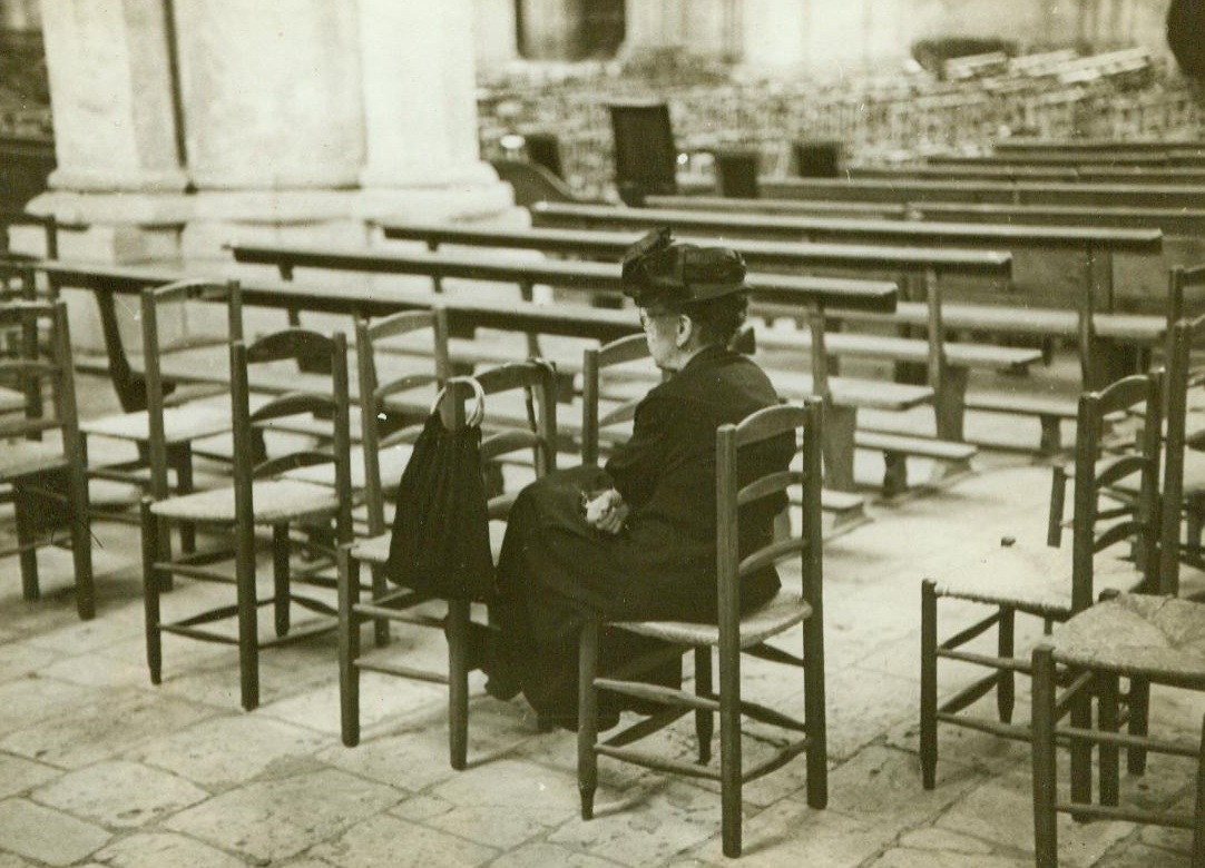 Giving Thanks In Her Way, 8/26/1944. Chartres, France -- While the streets outside are filled with crowds wildly cheering the liberation of Chartres by Yank Forces, this lone French woman sits quietly in the Cathedral giving thanks in her own way. Later the Cathedral  will be filled as the townspeople gather for Thanksgiving services. 8/26/44 (ACME);