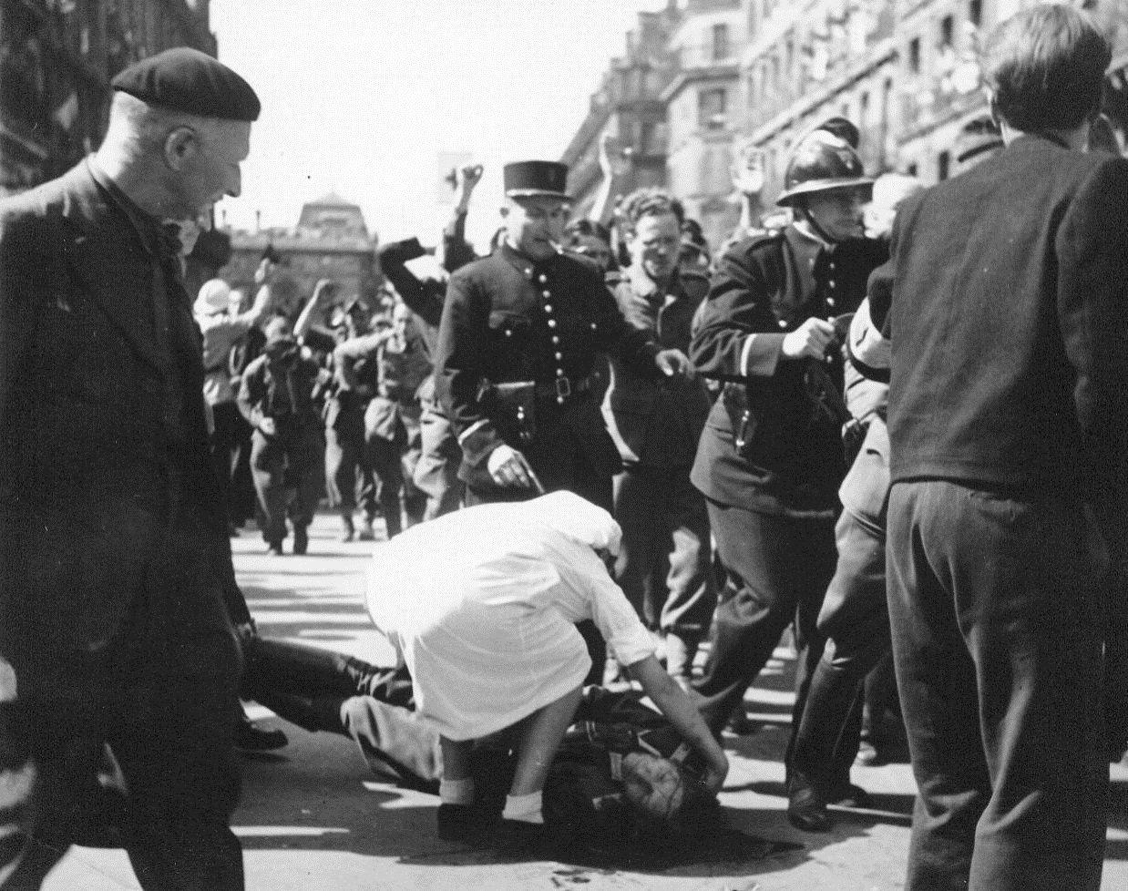 Resistance Roundup, 8/28/1944. Paris -- Lying wounded in the street, a German Officer gets the attention of a Red Cross worker as French patriots round up Nazis and collaborators  after street fighting in liberated Paris. Resistance snipers still terrorize the populace of the French capital. The allies have left the job of restoring order in Paris to the French. 8/28/44 (ACME);