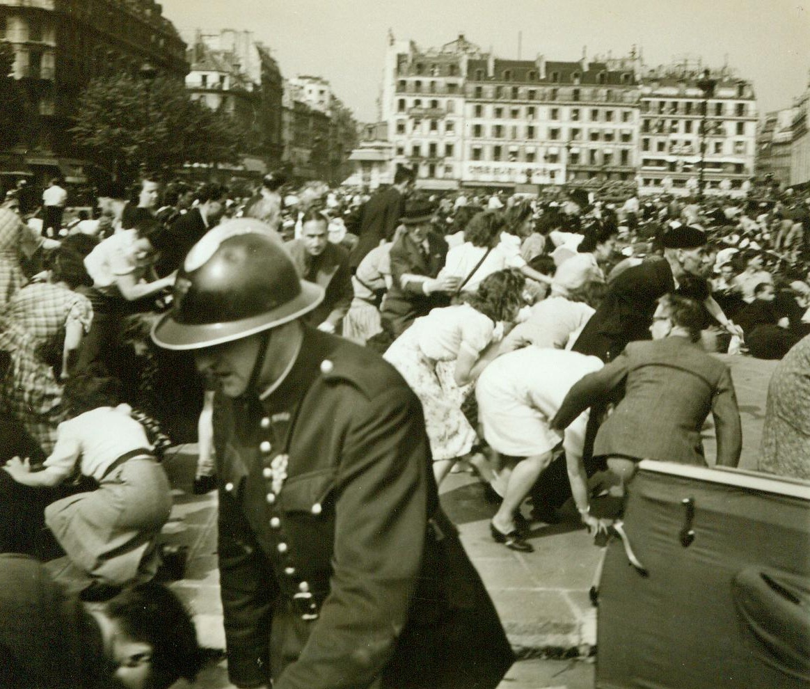 Panic In Paris, 8/28/1944. Paris -- Bending low and scurrying for cover, frightened Parisians try to escape the bullet whistling down from rooftop sniper nests. Panic reigned as street fighting broke up the official reception of General Charles De Gaulle in the French capital. 8/28/44 (ACME);