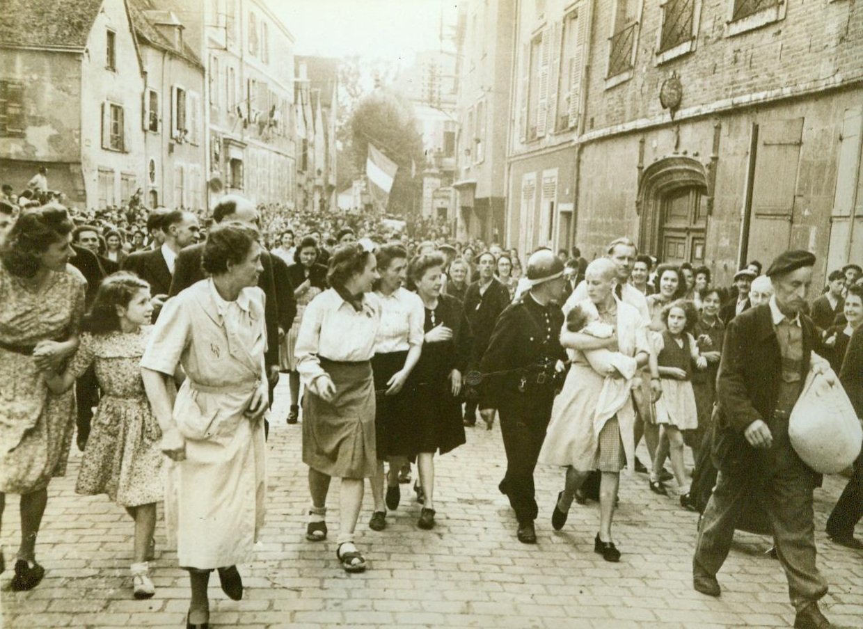 Collaborationist Is Scorned By Her People, 8/26/1944. Chartres, France -- Followed by jeering townspeople, a woman collaborator is led back to her home after having her hair shaved off. The shorn woman carries a German baby. The French Tricolour (Background) flies from the middle of the street and American flags are hung out of windows as French people celebrate the liberation of Chartres by the Yanks. 8/26/44 (ACME);