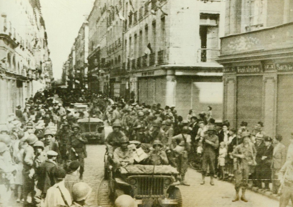 Cheering Patriots Line The Road, 8/6/1944. Rennes, France -- Natives of rennes, both young and old, line the sides of this street in the liberated city, raising their voices to cheer the victorious Yanks. Our warriors returned the cheers as they marched or rode through the heart of the Breton capital. 8/6/44 (ACME);