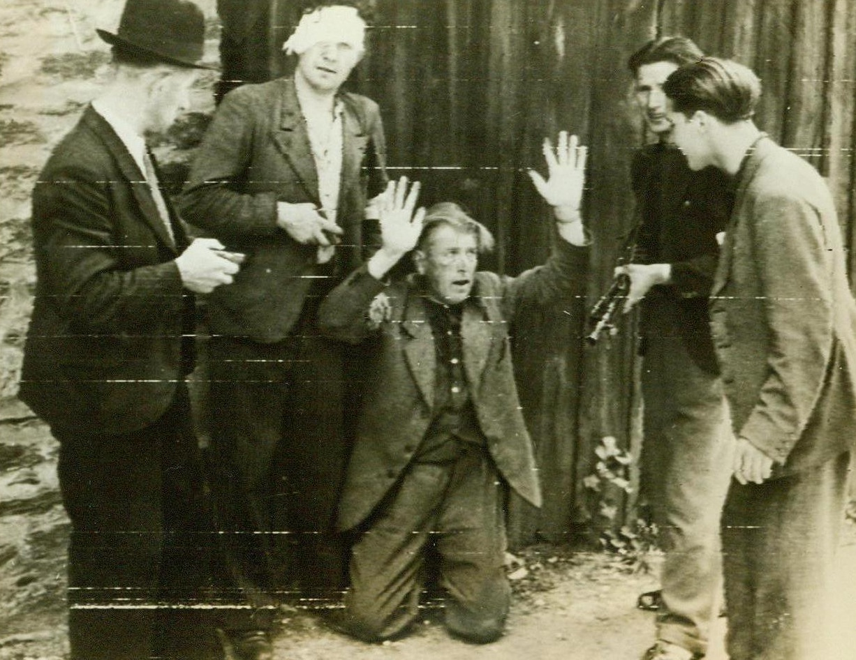 Collaborators Punishment, 8/6/1944. Rennes, France -- In partial payment for his crime of collaborating with the Nazis who dominated Rennes, this traitor is forced to kneel and shout the praises of De Gaulle and Churchill. He looks fearfully at patriots who rounded up disloyal Frenchmen as soon as the capital of Brittany fell to the Allies. 8/6/44 (ACME);