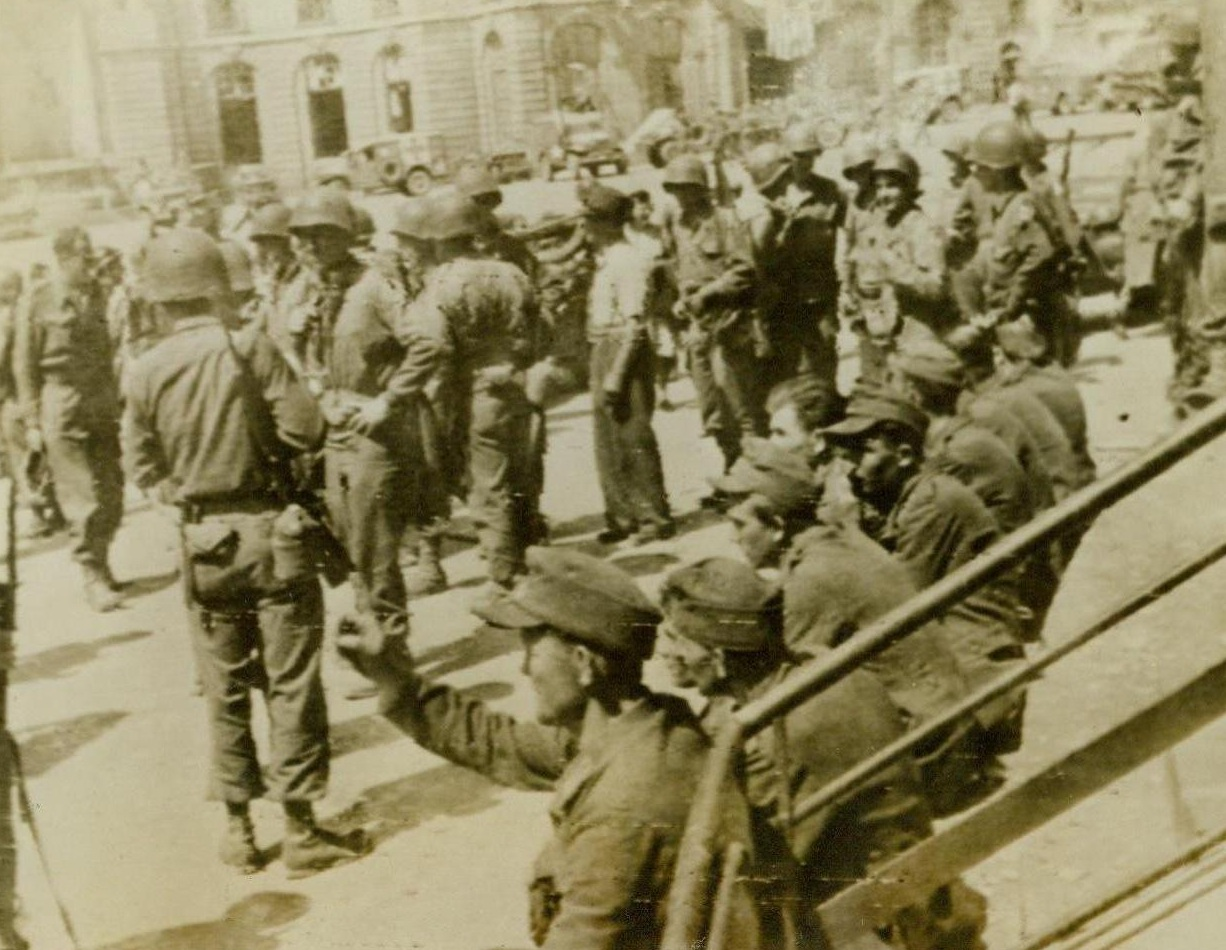 The Defeated, 8/6/1944. Rennes, France -- The liberation of Rennes, largest city to fall to the armies of liberation since the invasion of France, meant captivity for this handful of German prisoners. The beaten Nazis are shown outside Rennes City Hall. 8/6/44 (ACME);
