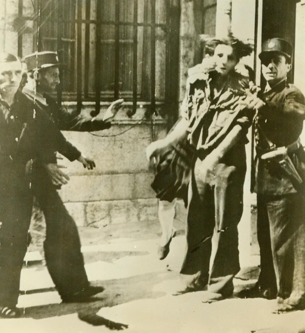 Aroused Avenger Gets Even, 8/22/1944. France -- An enraged woman (rear) tears at a captured Gestapo agent as Gendarmes attempt to placate her. The Gestapo man was responsible for the mutilation of her husband when the Nazis occupied the town of Brignoles, in Southern France. 8/22/44 (ACME);