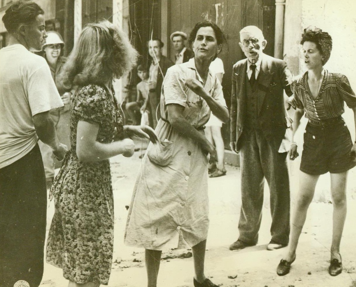 French Women Have It Out, 8/31/1944. France -- Two women, one a pro-Nazi, the other a patriot, engage in a street bout in a town in Southern France. A girl in shorts verbally blasts the Nazi-lover and an old man standing aside adds his thoughts of hatred into the fray. Women in center is object of derisive side glances from all who pass. With the liberation of this town, Brignoles, many of the men and women who were Nazi sympathizers were immediately rounded up by the Free French Partisans. 8/21/44 (ACME);