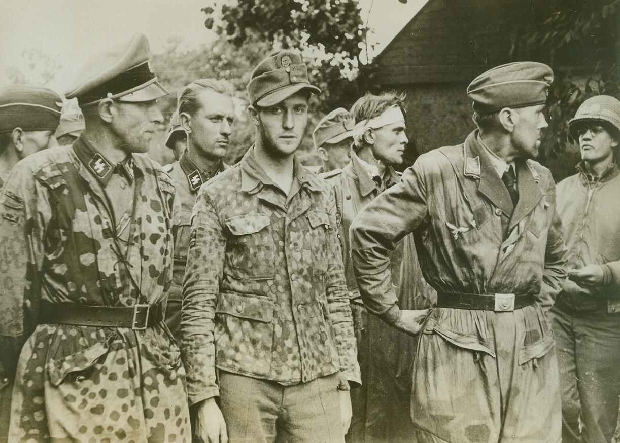 """Cream of the Wehrmacht, 8/8/1944. FRANCE – Their faces hard and sullen, mirroring the determination that made their crack SS division (the Second Armored) fight almost to the last man against Allied arms, these Nazi officers of the famous """"Goek von Berltchingen"""" regiment are lined up by their American captors, near Avranche. Credit: (ACME) (WP);"""