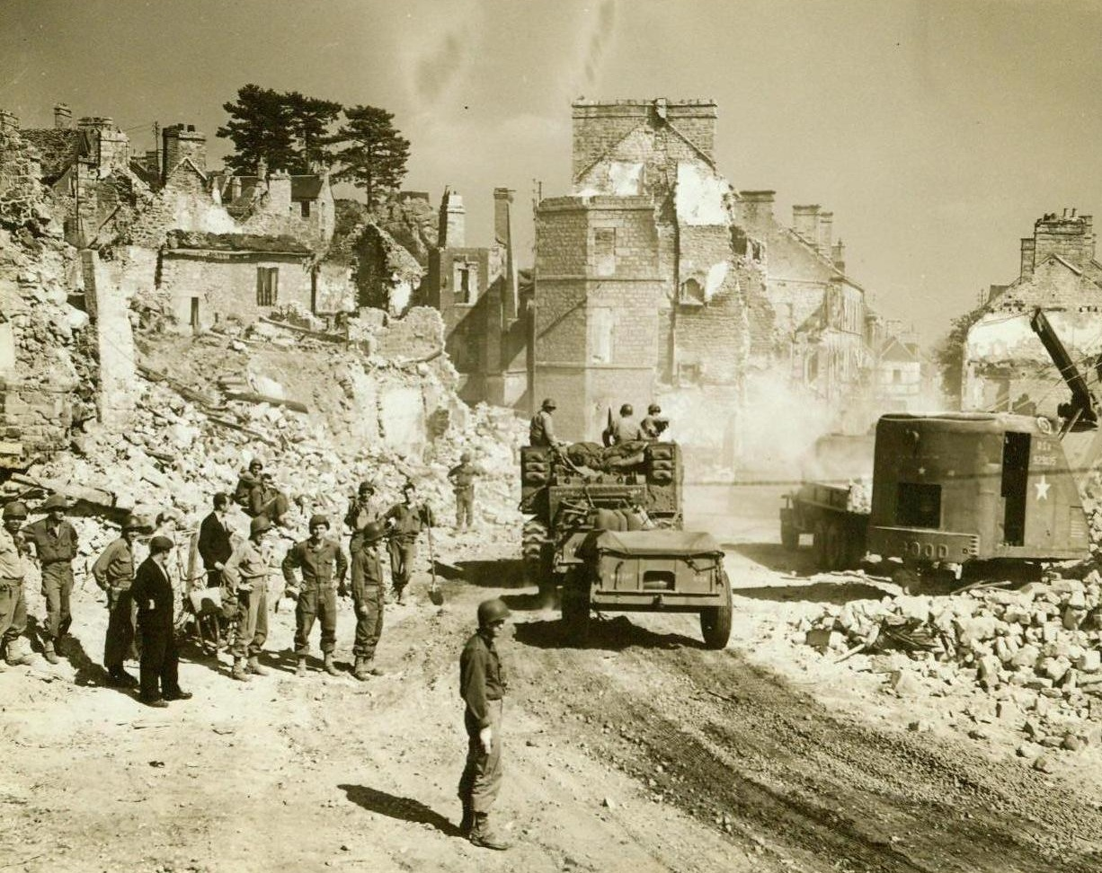 Erasing The Scars, 8/21/1944. France – As American troops race toward Paris, U.S. Army equipment begins to erase the battle scars from French towns along the way. Here a mechanical shovel clears great piles of rubble from this road in a battered town, permitting passage by heavier, front-bound vehicles 8/21/44 (ACME Photo By Bert Brandt, For The War Picture Pool);