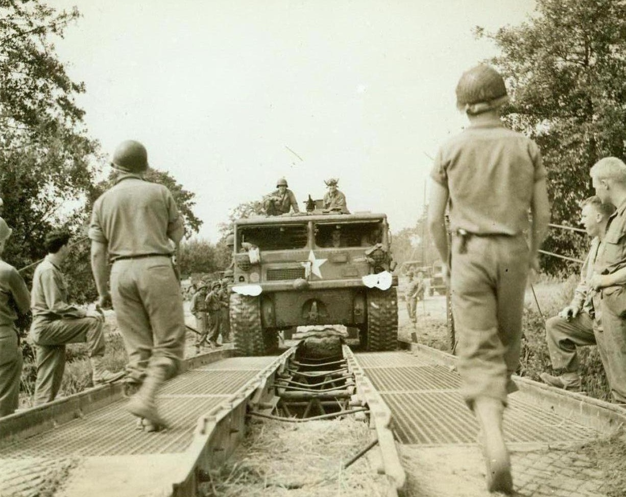 Rebuilding As They Go, 8/21/1944. France – On the heels of rapidly advancing American forces in France, Yank engineers are quickly repairing and rebuilding roads and bridges wrecked by the retreating enemy. This prime mover pulls artillery equipment over a treadway bridge speedily erected by the Americans. 8/21/44 (ACME Photo By Bert Brandt  For The War Picture Pool);
