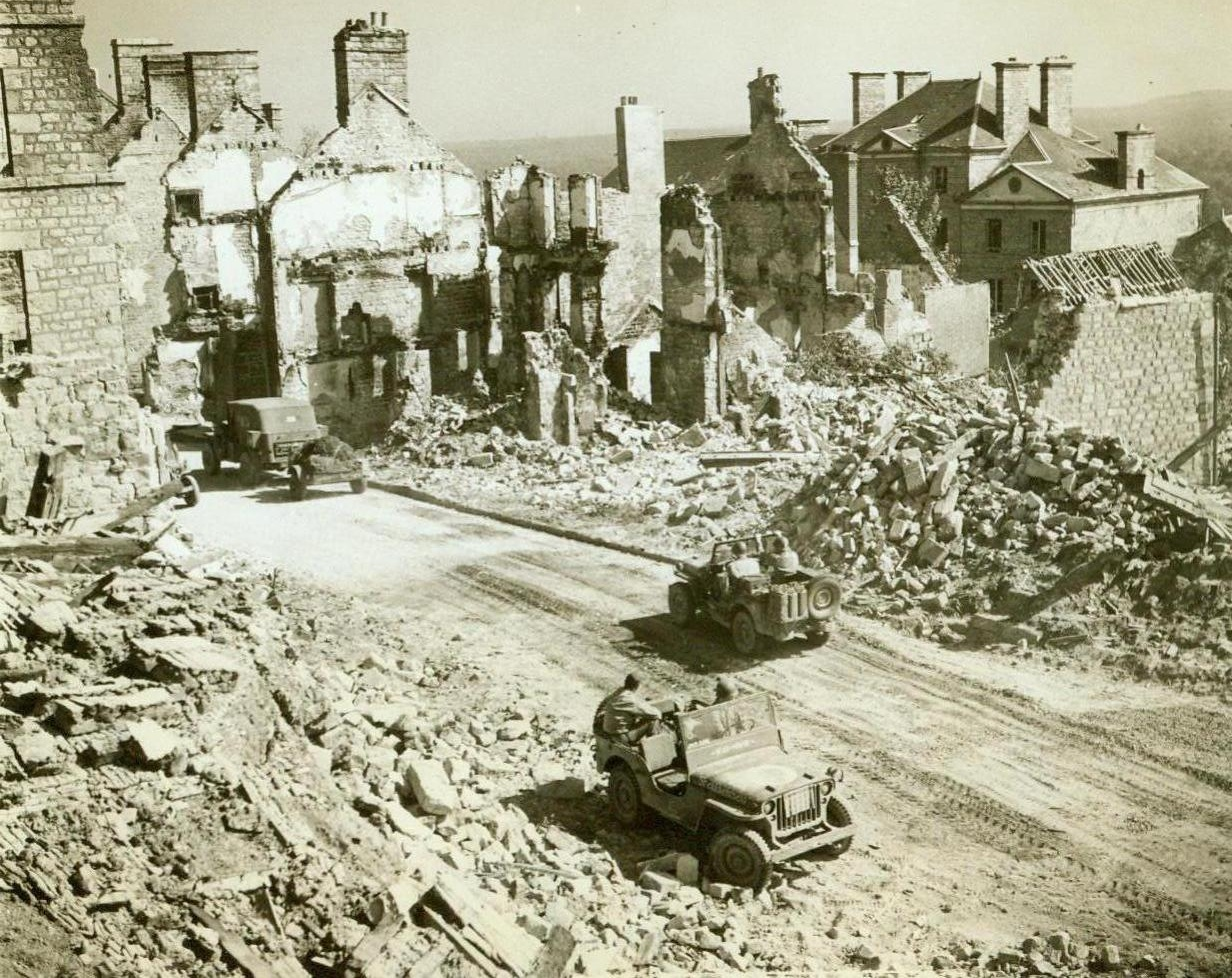 Past The Ruins To Paris, 8/21/1944. France – The crumbled ruins of buildings wrecked by bombs and shells line the sides of the road to Paris. American vehicles move up past this battered town, forging ahead to support the Third Army's lighting advance on the French capital. 8/21/44 (ACME Photo By Bert Brand For The War Picture Pool);