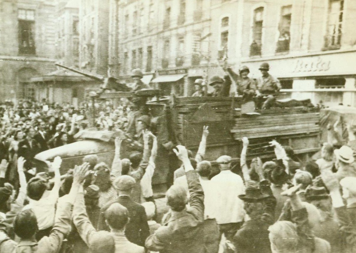 Hail The Heroes, 8/6/1944. Rennes, France – Wildly cheering, joyous natives of Rennes crowd around to welcome victorious Yanks into the liberated city. Waving and smiling from their armored vehicles, as the warriors return the greeting. 8/6/44 (Signal Corps Radiotelephoto from ACME);