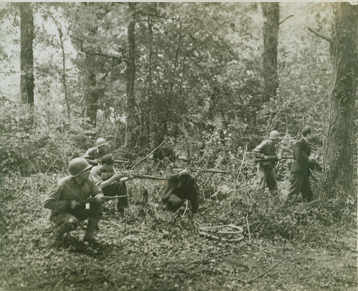 French Patriots Join Yanks, 8/5/1944. FRANCE -- American soldiers get valuable assistance from a group of French patriots in hunting down Nazi snipers during mop up operations in a wooded sector outside a town. In Brittany these patriots have given invaluable aid and are credited with being partly responsible for the great speed of the American push. Credit: (ACME);
