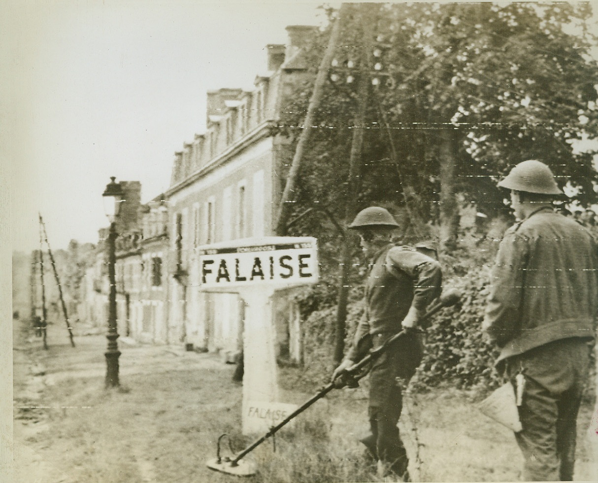 Mine Sweepers, 8/18/1944. FALAISE, FRANCE -- Canadian sappers search for mines along the grass borders lining the streets of Falaise as they enter the town taken in the drive toward Paris. Credit (Signal Corps Radiotelephoto from ACME);