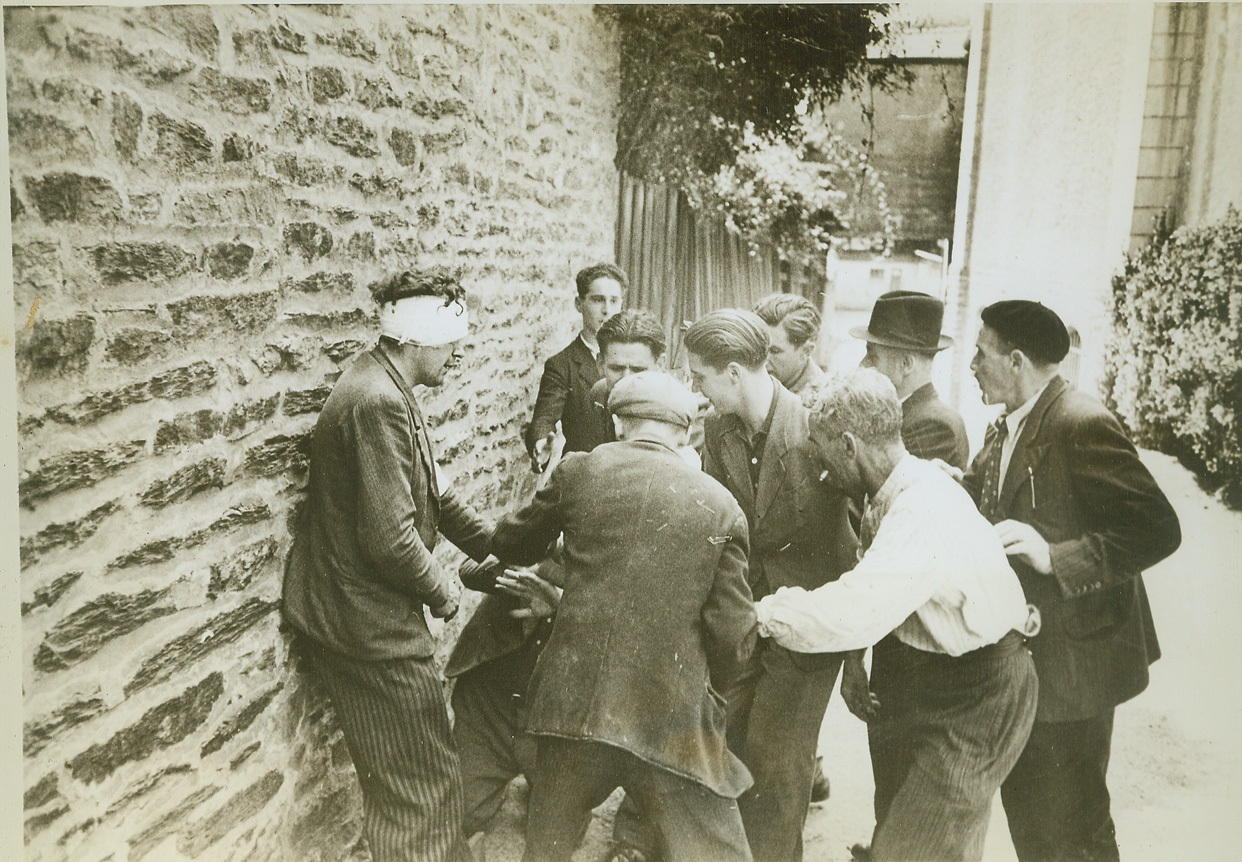 Paying for His Treachery, 8/12/1944. RENNES, FRANCE -- Angry citizens of Rennes wreak vengeance on a collaborator, captured after the Allies took the town. With his back against a wall, the traitor tries vainly to protect himself from blows of the angry people. (Man with bandage is not collaborator).  Credit (ACME) (WP);