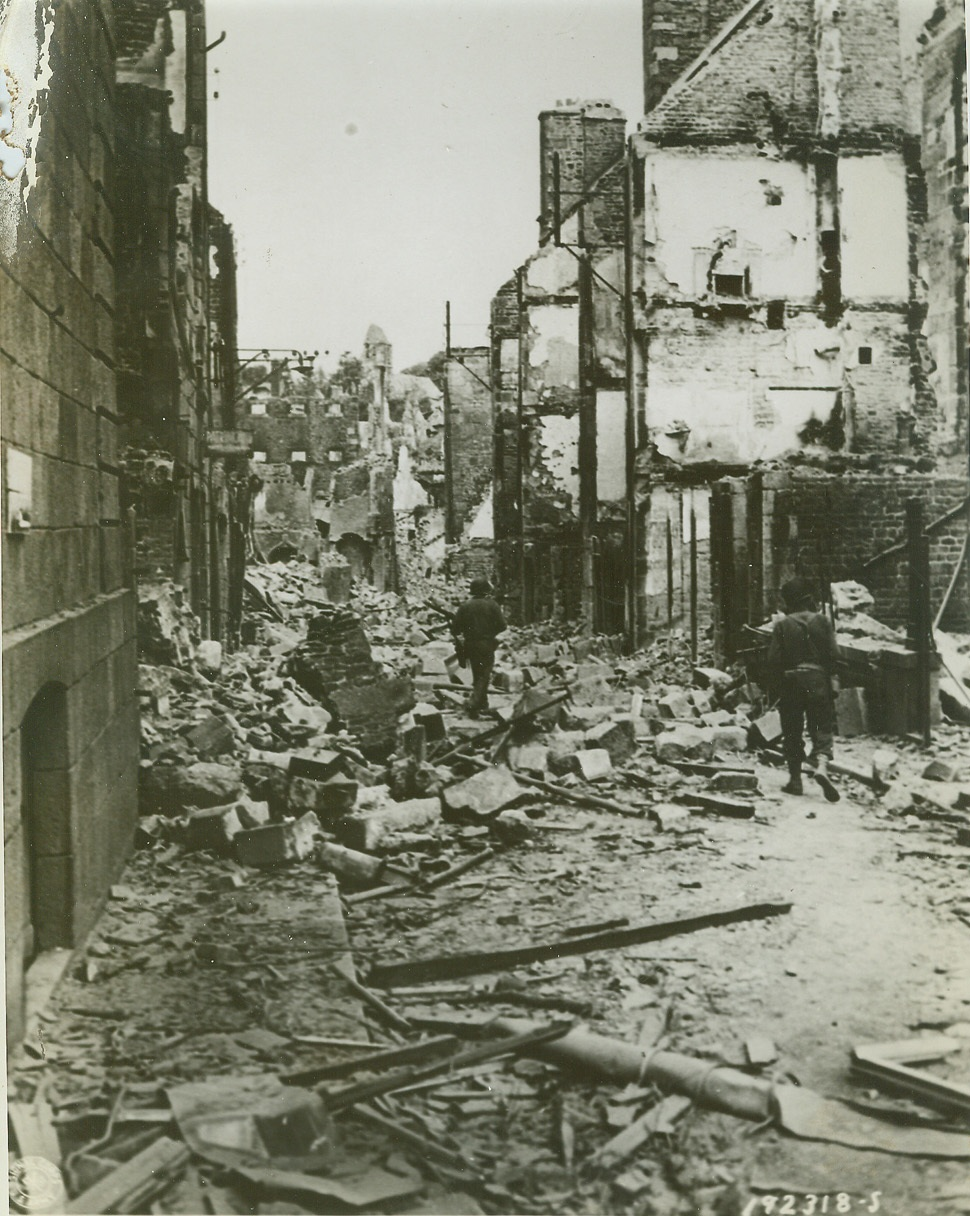 Here Lies Vire, 8/14/1944. VIRE, FRANCE -- Allied soldiers make their way through this street in Vire, scrambling over the debris which blocks their way. The French city was laid in ruins by the terrific bombardment preceding the Allied entry into the city. Credit (US Army Official Photo from ACME);