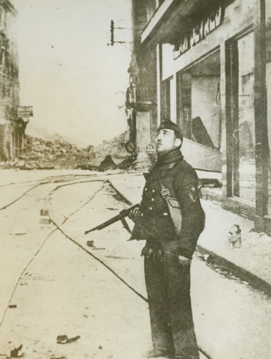 Caen During German Occupation, 8/1/1944. CAEN, FRANCE -- According to the German caption accompanying this photo received in London from a neutral source, this is a street in Caen after a British bombing attack which preceded its land onslaught on the city. A German soldier looks upward at the retreating planes. Credit (ACME);