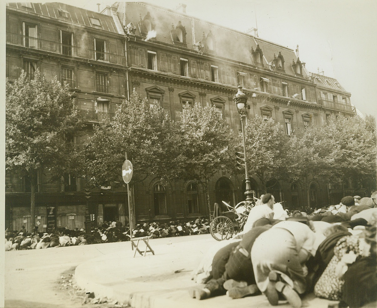 Bullets -- Unwelcome Guest at Celebration, 8/30/1944. FRANCE -- Part of the huge crowd gathered to pay tribute to Gen. Charles De Gaulle as he entered liberated Paris, crouch for cover as enemy sniper fire breaks up the celebration. Note the gun flash from the top floor, center, of the building at left and the smoke from gunfire still lingering in the air. Credit -WP-(ACME Photo by Andrew Lopez, War Pool Correspondent);